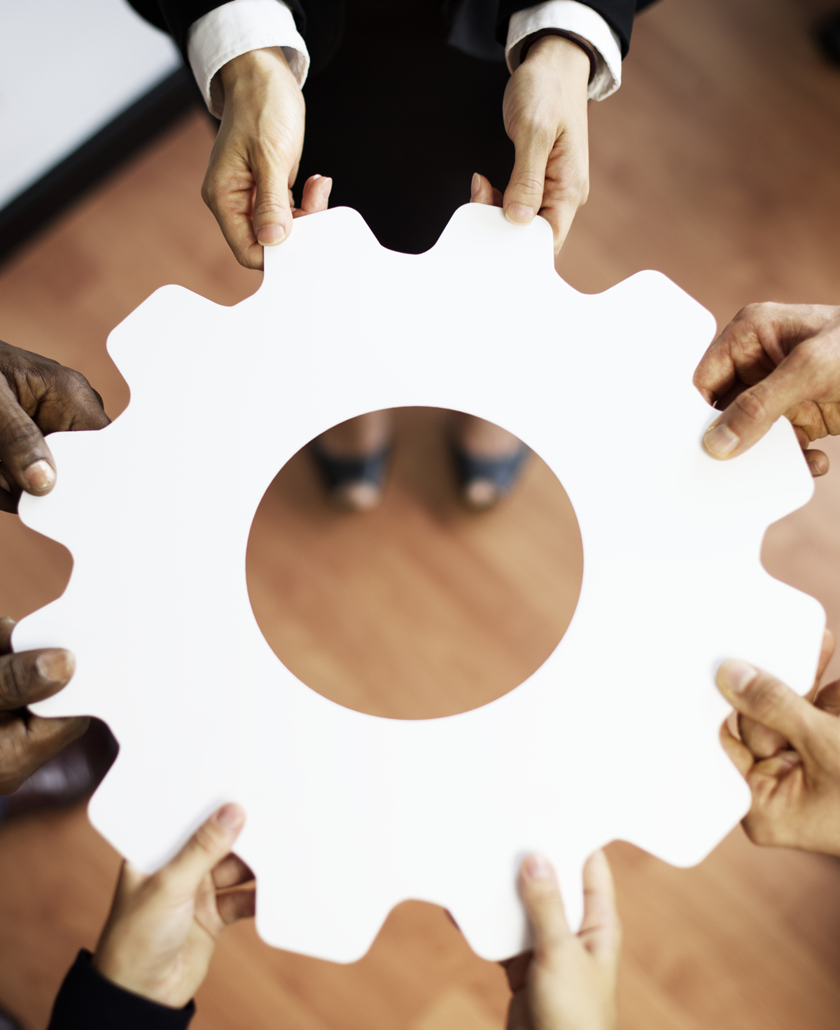business people holding a large cog